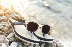 黑色在的被反映的太阳镜石头 从玻璃的阴影 阳光 背景概念框架沙子贝壳夏天 库存照片