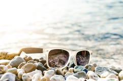 黑色在的被反映的太阳镜石头 从玻璃的阴影 阳光 背景概念框架沙子贝壳夏天 WomanÂ的腿 免版税库存图片