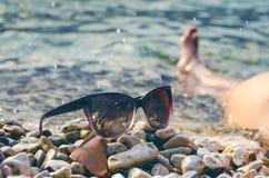 黑色在的被反映的太阳镜石头 从玻璃的阴影 阳光 背景概念框架沙子贝壳夏天 WomanÂ的腿 库存照片