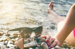 黑色在的被反映的太阳镜石头 从玻璃的阴影 阳光 背景概念框架沙子贝壳夏天 WomanÂ的腿 免版税图库摄影