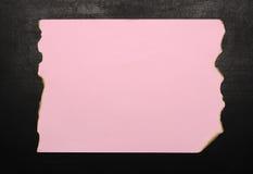 紫色在黑板的被烧的纸 免版税库存照片
