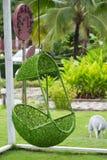 绿色垂悬的椅子在庭院里 免版税库存图片