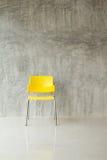黄色塑料椅子 免版税库存照片