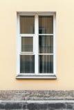 黄色墙壁和窗口在白色框架 免版税库存照片