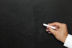 黑色墙壁 有白色白垩的空的黑板或黑板手 空位 库存照片