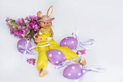 黄色复活节陶瓷兔宝宝用紫色鸡蛋 免版税库存图片