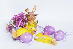 黄色复活节陶瓷兔宝宝用紫色鸡蛋 库存照片