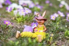 黄色复活节陶瓷兔宝宝用紫色鸡蛋 免版税图库摄影