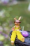 黄色复活节陶瓷兔宝宝用紫色鸡蛋 库存图片