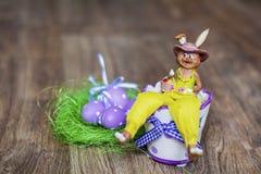 黄色复活节陶瓷兔宝宝用紫色鸡蛋 免版税库存照片