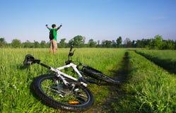 绿色夏天领域的骑自行车的人 库存照片