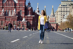 黄色外套的少妇在红场走在莫斯科 库存照片