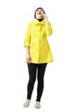黄色外套的愉快的年轻短发妇女大笑在手机的 库存照片