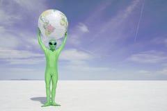 绿色外籍人拿着在白色沙漠行星上的地球地球 免版税库存图片