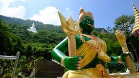绿色天使和大白色菩萨雕象在山 免版税库存图片