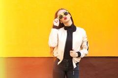 黄色太阳镜的年轻行家女孩亲吻在橙色墙壁上的 都市的样式 葡萄酒 强光和光 免版税图库摄影