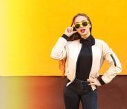 黄色太阳镜的年轻行家女孩微笑在橙色墙壁上的 都市的样式 葡萄酒 强光和光 免版税图库摄影