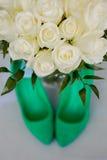 绿色婚礼鞋子和白色新娘花束  免版税图库摄影