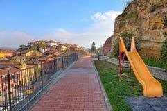 孩子在操场滑在小镇在意大利。 免版税库存照片