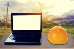 黄色安全帽和膝上型计算机在书桌上 免版税库存图片
