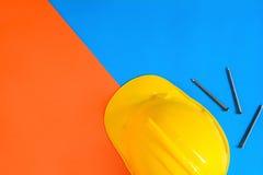 黄色安全帽和建筑材料在纸的蓝色 免版税库存照片