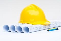 黄色安全帽和建筑计划 库存图片