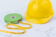 黄色安全帽和绿色测量的磁带 库存照片