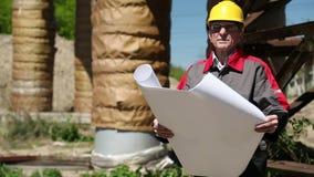 黄色安全帽的工作者有在热驻地的设计图的 股票录像