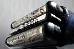 黑色宏观细节和刮胡子刀的银头有它锋利的剃须刀的在穿孔的金属栅格后 库存图片