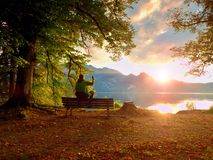 绿色室外夹克的人拍照片,坐长木凳在湖 免版税库存图片
