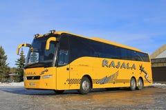 黄色富豪集团教练在冬天停放的公共汽车 免版税库存照片