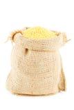 黄色小米填装的一个亚麻制大袋 免版税库存图片