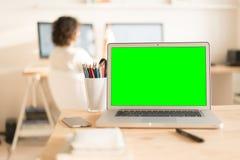 绿色屏幕便携式计算机和玻璃与铅笔在桌上 库存图片