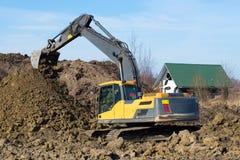 黄色履带牵引装置挖掘机在倾销土壤运转 库存照片