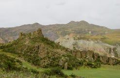 绿色山谷和岩层在多云天空下 免版税库存照片
