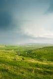 绿色山谷在多云天空下 库存图片