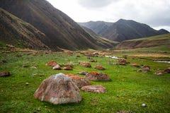 绿色山谷风景 在前景的大石头 山上面在背景中 库存图片