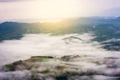 绿色山顶视图和日出与云彩的在多雨海 库存图片