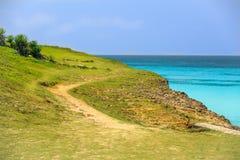 绿色峭壁美好,秀丽的看法在平静的海洋和明白蓝天的 免版税库存照片