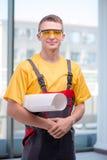 黄色工作服的年轻建筑工人 免版税库存照片