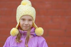 黄色帽子和桃红色夹克的小女孩 免版税图库摄影