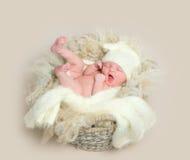 黄色帽子的甜打呵欠的婴孩 库存图片
