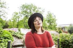 绿色庭院佩带的帽子的成熟深色的妇女,微笑,友好welkoming,生活方式人概念关闭  免版税库存照片