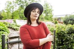 绿色庭院佩带的帽子的成熟深色的妇女,微笑,友好welkoming,生活方式人概念关闭  免版税库存图片