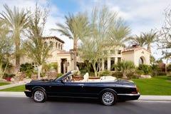 黑色开放屋顶汽车在豪宅前面停放了 库存图片