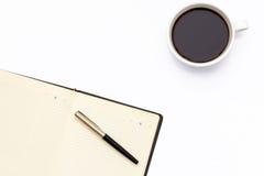 黑色开放日志、笔和杯在白色背景的无奶咖啡 库存图片