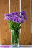 紫色开花在一块玻璃的花束在桌上 免版税库存图片