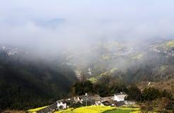 黄色强奸和村庄山坡的在春天,山雾盖子 免版税库存图片