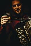 色彩手风琴球员和一杯酒精饮料 免版税库存图片