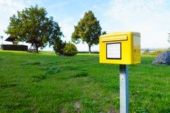黄色德国邮箱一在绿色草甸在村庄 库存图片